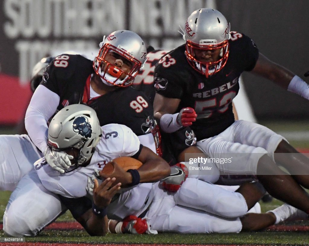 Quarterback Caylin Newton #3 of the Howard Bison is tackled after running for a six-yard gain by defensive lineman Mike Hughes Jr. #99 and linebacker Farrell Hester II #53 of the UNLV Rebels during their game at Sam Boyd Stadium on September 2, 2017 in Las Vegas, Nevada. Howard won 43-40.