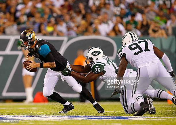 Quarterback Chad Henne of the Jacksonville Jaguars in action against Shelby Harris and Lawrence Thomas of the New York Jets in an NFL preseason game...