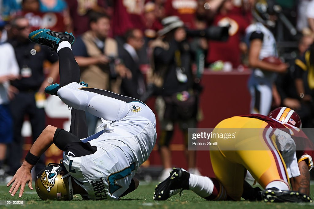 Quarterback Chad Henne of the Jacksonville Jaguars is hit by inside linebacker Perry Riley of the Washington Redskins in the second quarter at...