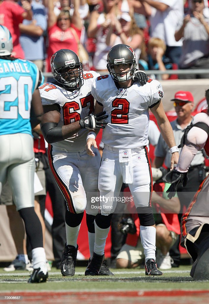 Quarterback Chris Simms #2 of the Tampa Bay Buccaneers is congratulated by Kenyatta Walker #67 during the game against the Carolina Panthers at Raymond James Stadium on September 24, 2006 in Tampa, Florida. The Panthers defeated the Buccaneers 26-24.