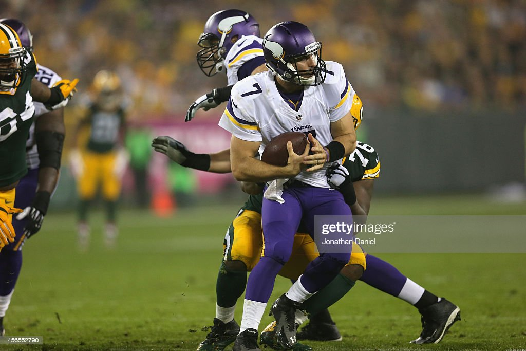 Quarterback Christian Ponder #7 of the Minnesota Vikings is sacked by Mike Daniels #76 of the Green Bay Packers in the second quarter at Lambeau Field on October 2, 2014 in Green Bay, Wisconsin.