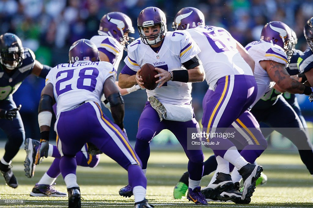 Quarterback Christian Ponder #7 of the Minnesota Vikings looks to hand off to running back Adrian Peterson #28 against the Seattle Seahawks at CenturyLink Field on November 17, 2013 in Seattle, Washington.