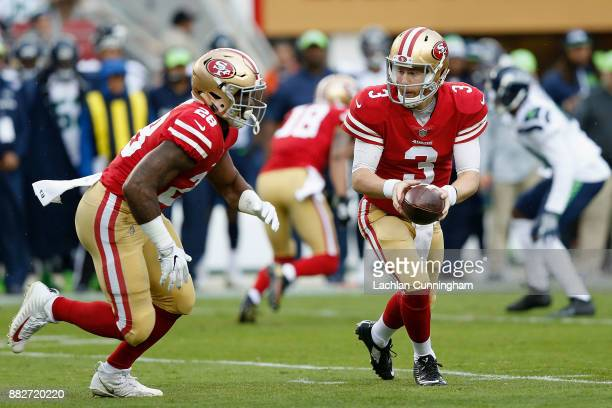 Quarterback CJ Beathard looks to hand off to running back Carlos Hyde of the San Francisco 49ers against the Seattle Seahawks at Levi's Stadium on...