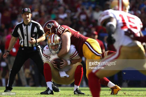 Quarterback CJ Beathard of the San Francisco 49ers is sacked by defensive tackle Matthew Ioannidis of the Washington Redskins during the second half...