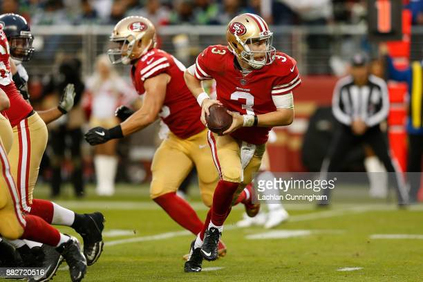 Quarterback CJ Beathard of the San Francisco 49ers looks to hand off the ball against the Seattle Seahawks at Levi's Stadium on November 26 2017 in...