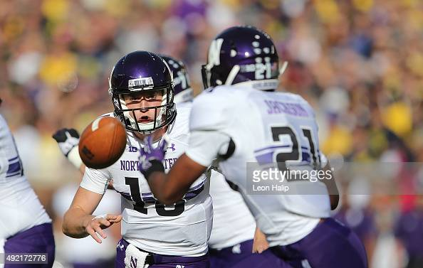 Quarterback Clayton Thorson of the Northwestern Wildcats pitches the ball to running back Justin Jackson of the Northwestern Wildcats during the...