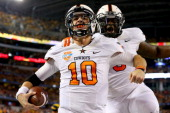 Quarterback Clint Chelf of the Oklahoma State Cowboys celebrates with Kye Staley after Chelf rushes for a 23yard touchdown in the fourth quarter...