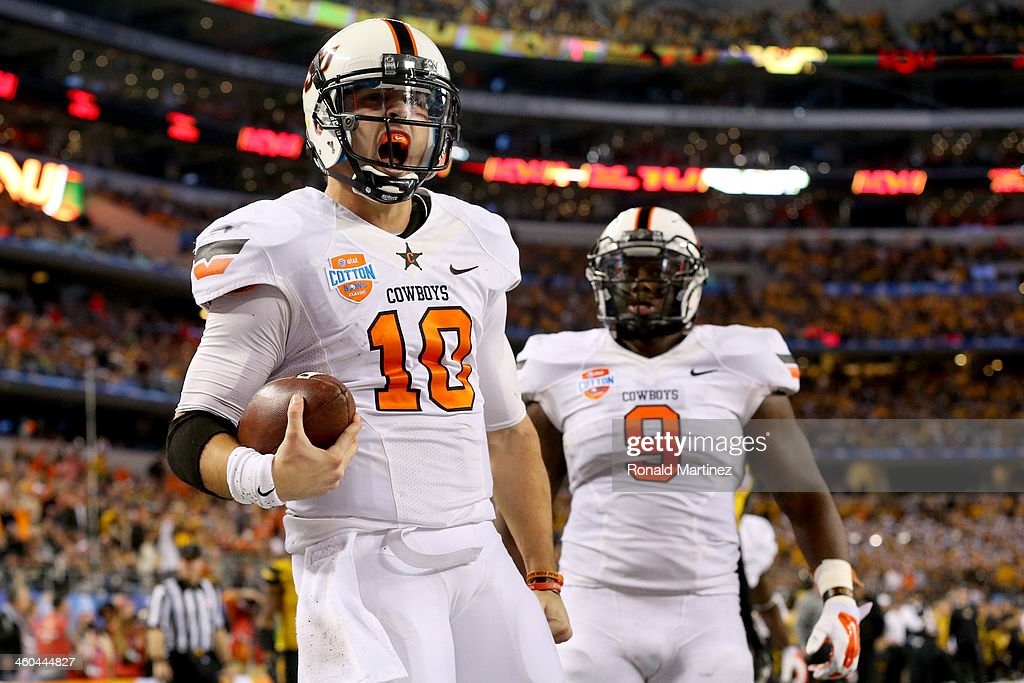 Quarterback Clint Chelf #10 of the Oklahoma State Cowboys celebrates with Kye Staley #9 after Chelf rushes for a 23-yard touchdown in the fourth quarter against the Missouri Tigers during the AT&T Cotton Bowl on January 3, 2014 in Arlington, Texas.