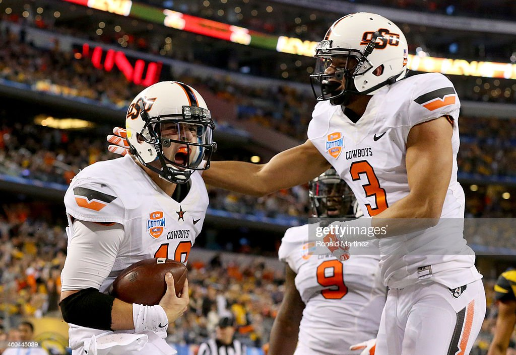 Quarterback Clint Chelf #10 of the Oklahoma State Cowboys celebrates with Marcell Ateman #3 after Chelf rushes for a 23-yard touchdown in the fourth quarter against the Missouri Tigers during the AT&T Cotton Bowl on January 3, 2014 in Arlington, Texas.