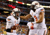 Quarterback Clint Chelf of the Oklahoma State Cowboys celebrates with Marcell Ateman after Chelf rushes for a 23yard touchdown in the fourth quarter...
