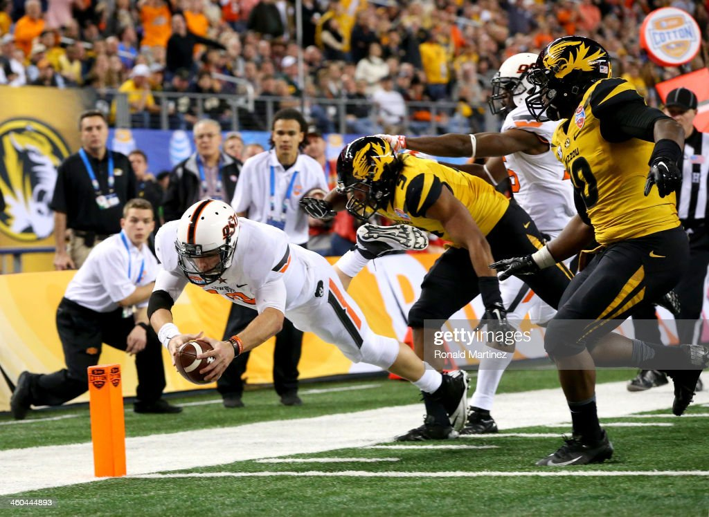 Quarterback Clint Chelf #10 of the Oklahoma State Cowboys dives into the endzone for a 23-yard rushing touchdown in the fourth quarter against the Missouri Tigers during the AT&T Cotton Bowl on January 3, 2014 in Arlington, Texas.
