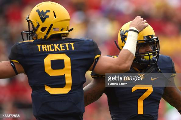 Quarterback Clint Trickett of the West Virginia Mountaineers celebrates running back Rushel Shell first quarter touchdown against the Maryland...