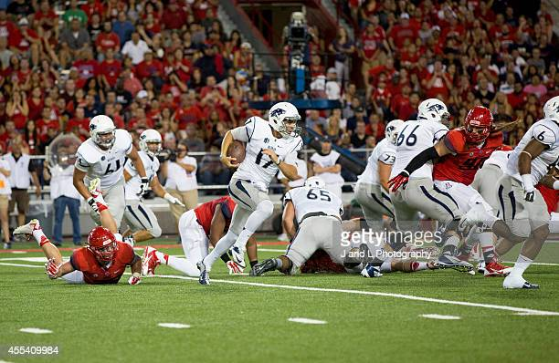 Quarterback Cody Fajardo of the Nevada Wolf Pack runs for a short gain in the second quarter against the Arizona Wildcats at Arizona Stadium on...