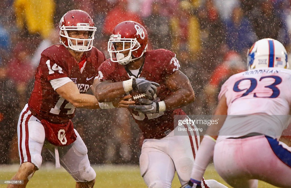 Quarterback Cody Thomas #14 hands off to running back Samaje Perine #32 of the Oklahoma Sooners during the game against the Kansas Jayhawks November 22, 2014 at Gaylord Family-Oklahoma Memorial Stadium in Norman, Oklahoma. The Sooners defeated the Jayhawks 44-7.