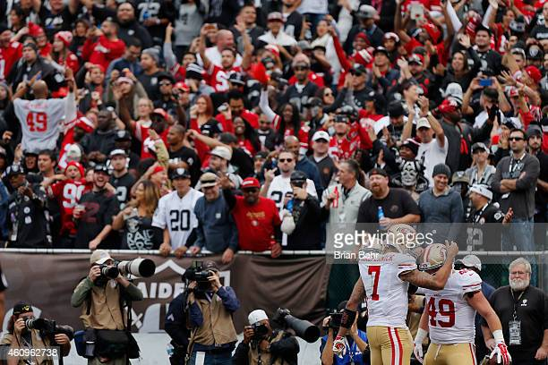 Quarterback Colin Kaepernick congratulates fullback Bruce Miller of the San Francisco 49ers on an eightyard touchdown against the Oakland Raiders in...