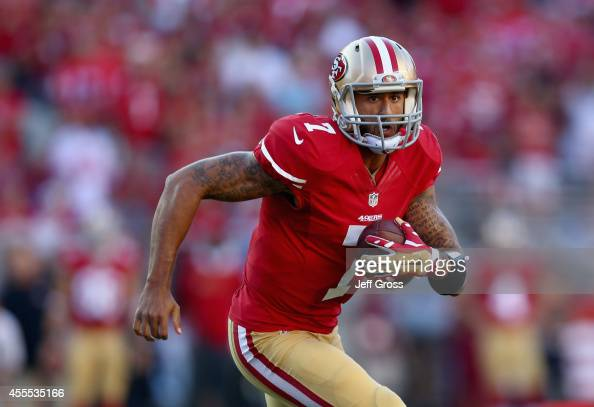 Quarterback Colin Kaepernick of the San Francisco 49ers carries the ball against the Chicago Bears at Levi's Stadium on September 14 2014 in Santa...