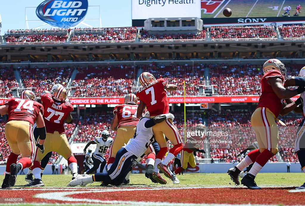 Quarterback <a gi-track='captionPersonalityLinkClicked' href=/galleries/search?phrase=Colin+Kaepernick&family=editorial&specificpeople=5525694 ng-click='$event.stopPropagation()'>Colin Kaepernick</a> #7 of the San Francisco 49ers gets hit as he throws by one of the San Diego Chargers at Levi's Stadium on August 24, 2014 in Santa Clara, California.