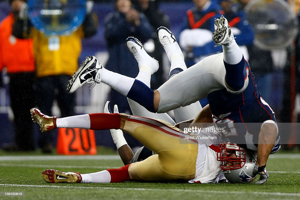 Quarterback Colin Kaepernick of the San Francisco 49ers gets sacked by defensive end Rob Ninkovich and defensive end Justin Francis of the New...