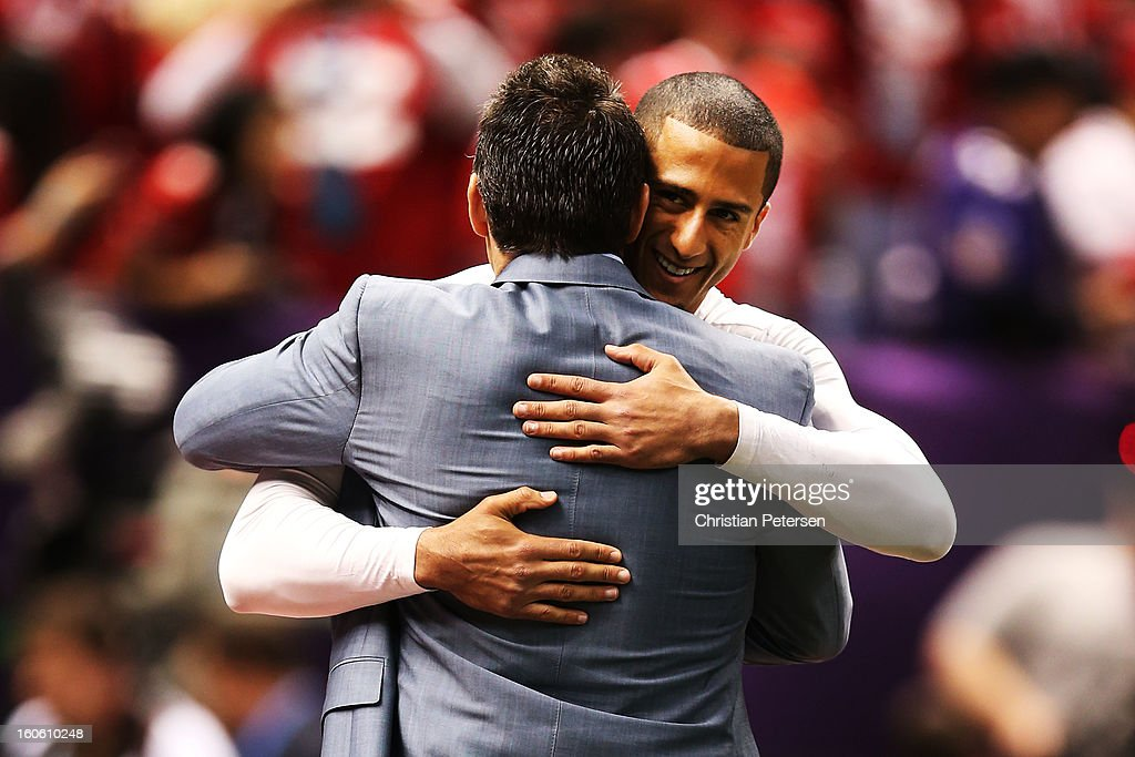 Quarterback Colin Kaepernick #7 (R) of the San Francisco 49ers hugs NFL Network analyst Kurt Warner during warm ups prior to Super Bowl XLVII against the Baltimore Ravens at the Mercedes-Benz Superdome on February 3, 2013 in New Orleans, Louisiana.