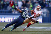 Quarterback Colin Kaepernick of the San Francisco 49ers is sacked by outside linebacker KJ Wright of the Seattle Seahawks at CenturyLink Field on...