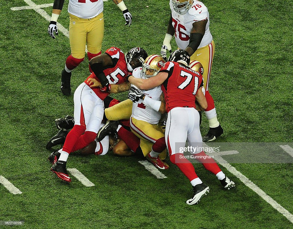 Quarterback Colin Kaepernick #7 of the San Francisco 49ers is tackled by Kroy Biermann #71 and Stephen Nicholas #54 of the Atlanta Falcons during the NFC Championship game at the Georgia Dome on January 20, 2013 in Atlanta, Georgia.