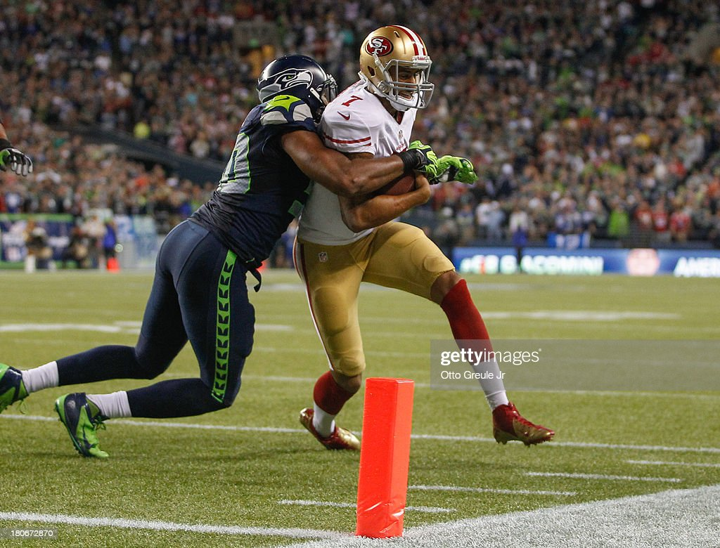 Quarterback <a gi-track='captionPersonalityLinkClicked' href=/galleries/search?phrase=Colin+Kaepernick&family=editorial&specificpeople=5525694 ng-click='$event.stopPropagation()'>Colin Kaepernick</a> #7 of the San Francisco 49ers is tackled short of the goal line by outside linebacker K.J. Wright #50 of the Seattle Seahawks at CenturyLink Field on September 15, 2013 in Seattle, Washington. The Seahawks defeated the 49ers 29-3.