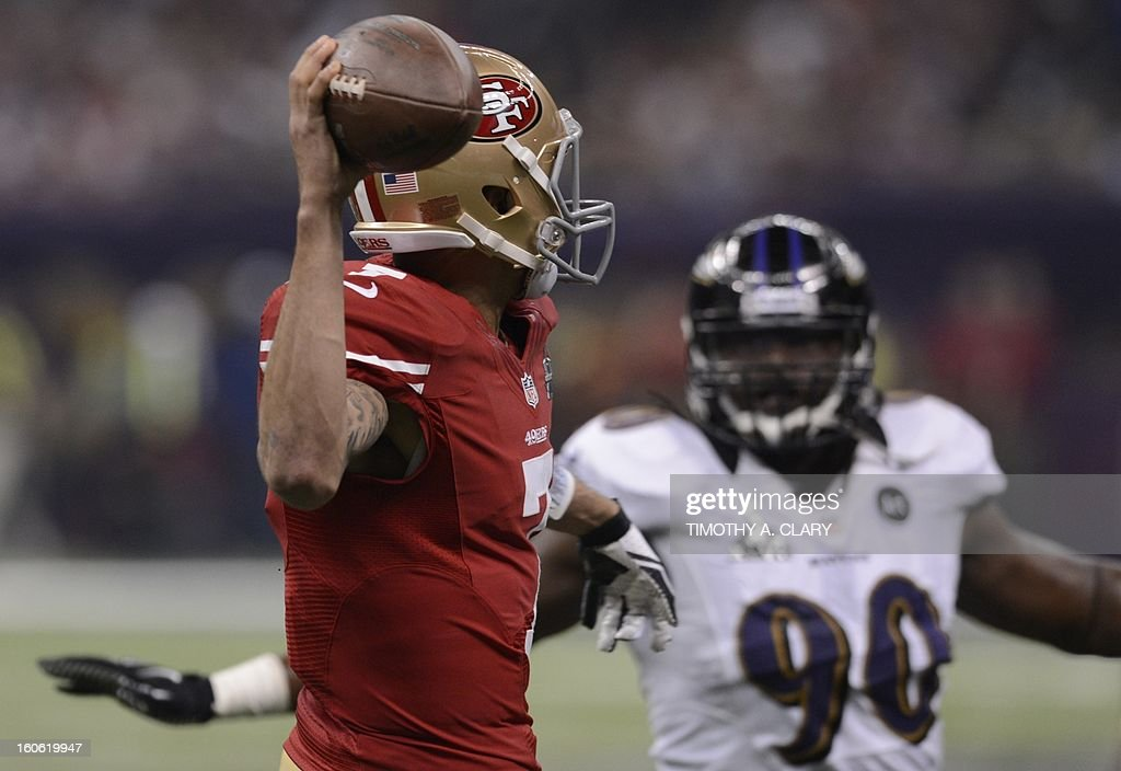 Quarterback Colin Kaepernick (L) of the San Francisco 49ers looks to pass against Pernell McPhee (R) of the Baltimore Ravens during Super Bowl XLVII at the Mercedes-Benz Superdome on February 3, 2013 in New Orleans, Louisiana.