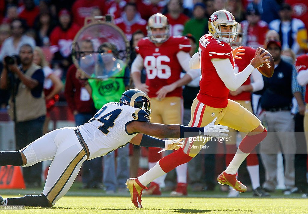 Quarterback <a gi-track='captionPersonalityLinkClicked' href=/galleries/search?phrase=Colin+Kaepernick&family=editorial&specificpeople=5525694 ng-click='$event.stopPropagation()'>Colin Kaepernick</a> #7 of the San Francisco 49ers runs for a first down against defensive end Robert Quinn #94 of the St. Louis Rams in the fourth quarter on November 11, 2012 at Candlestick Park in San Francisco, California. The teams tied 24-24 in overtime.