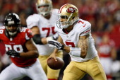Quarterback Colin Kaepernick of the San Francisco 49ers runs with the ball against defensive end Cliff Matthews of the Atlanta Falcons in the second...