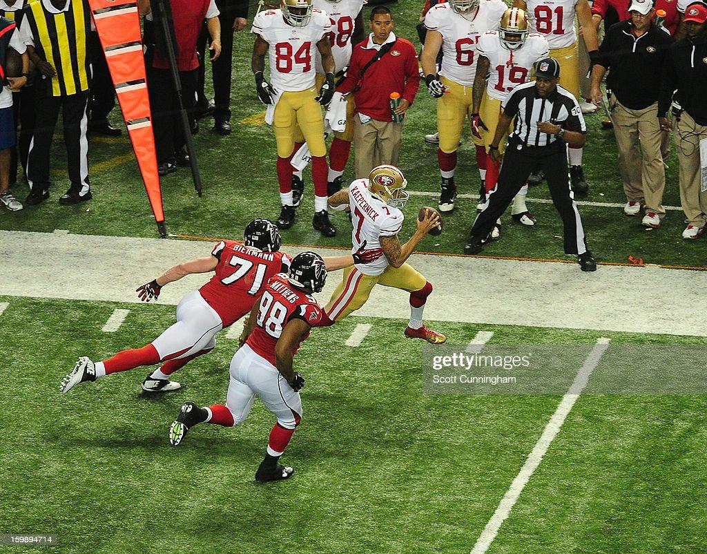 Quarterback Colin Kaepernick of the San Francisco 49ers scrambles against Kroy Biermann and Cliff Matthews of the Atlanta Falcons during the NFC...