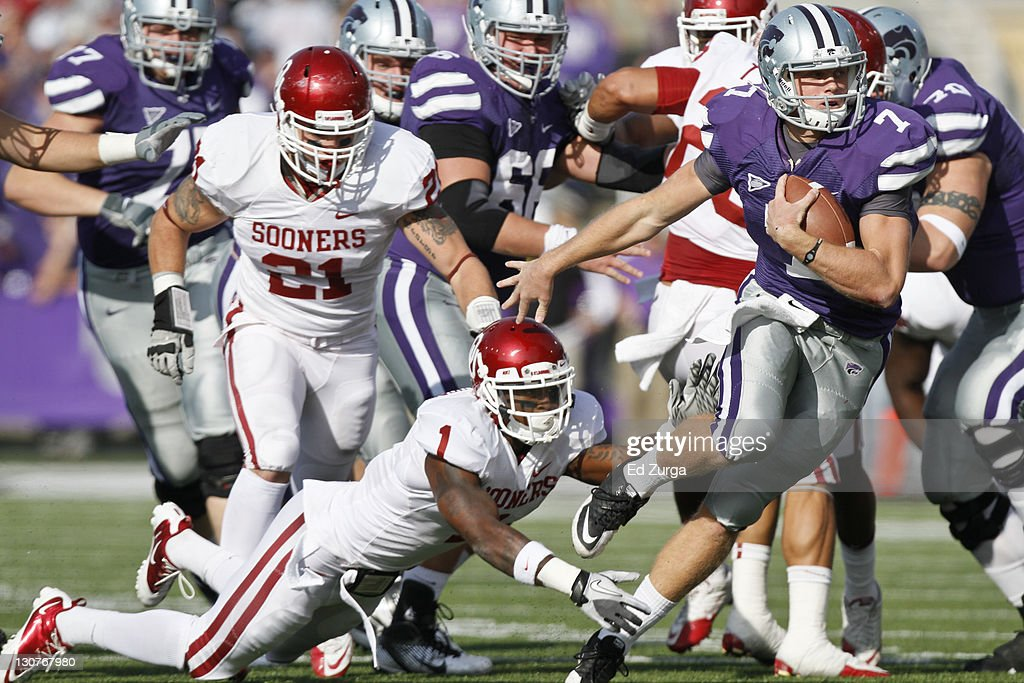 Quarterback Collin Klein #7 of the Kansas State Wildcats slips past Tony Jefferson #1 and Tom Wort #21 of the Oklahoma Sooners as he runs for a touchdown in the second quarter at Bill Snyder Family Stadium on October 29, 2011 in Manhattan, Kansas.