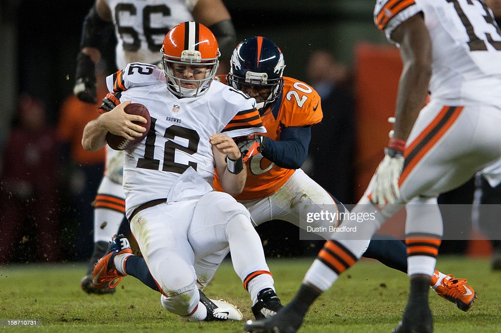 Quarterback Colt McCoy #12 of the Cleveland Browns is tackles as he rushes by strong safety Mike Adams #20 of the Denver Broncos during a game at Sports Authority Field at Mile High on December 23, 2012 in Denver, Colorado. The Broncos defeated the Browns 34-12.