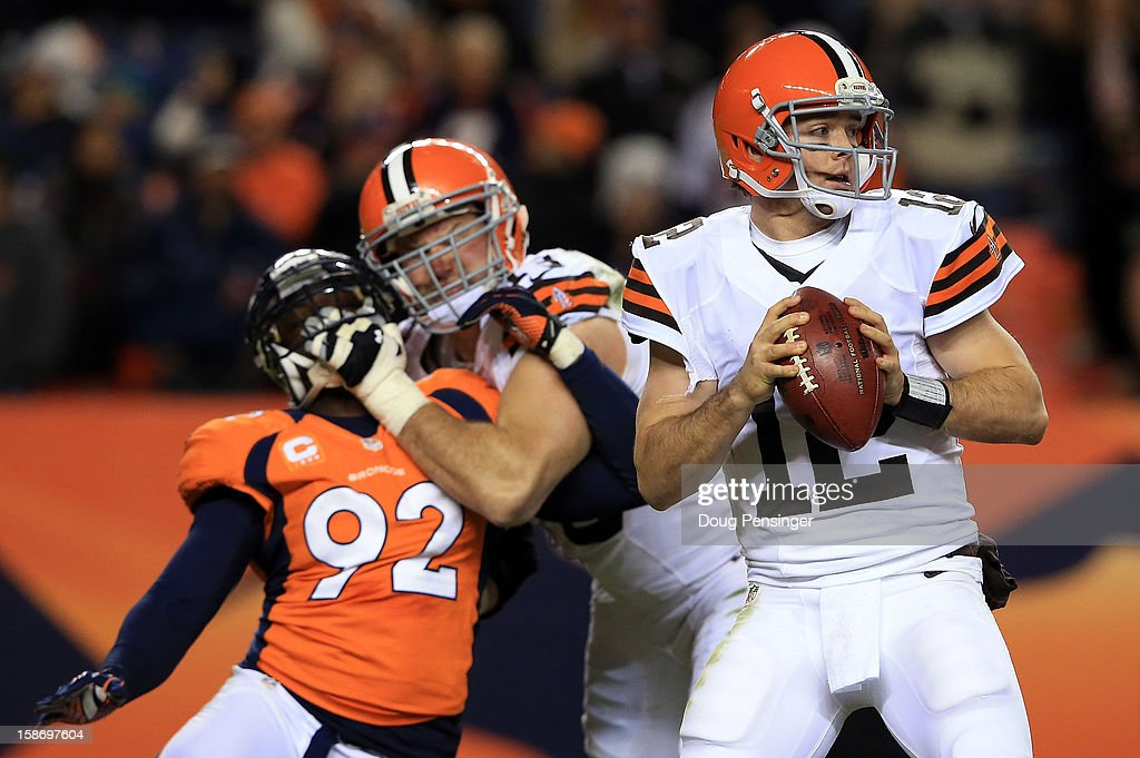 Quarterback Colt McCoy #12 of the Cleveland Browns looks for a receiver as tackle Joe Thomas #73 of the Cleveland Browns blocks defensive end Elvis Dumervil #92 of the Denver Broncos at Sports Authority Field at Mile High on December 23, 2012 in Denver, Colorado. The Broncos defeated the Browns 34-12.