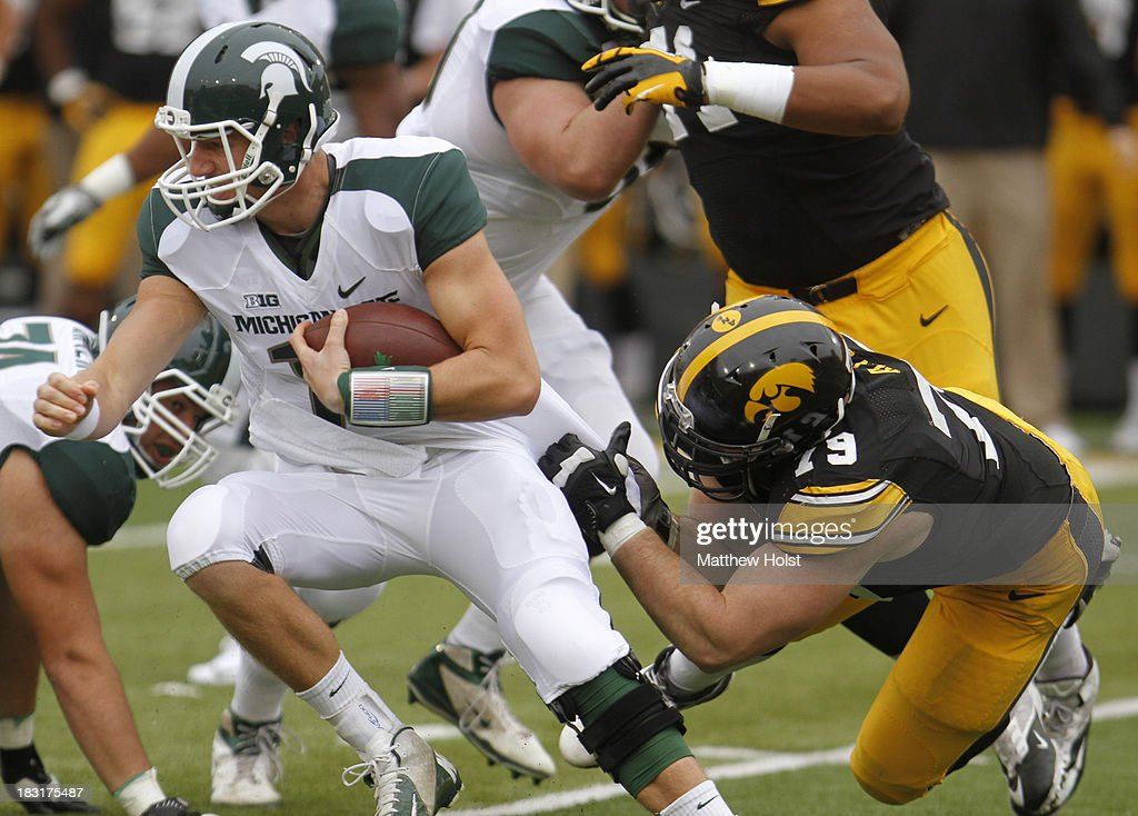 Quarterback Connor Cook #18 of the Michigan State Spartans breaks a tackle during the first quarter by defensive lineman Dominic Alvis #79 of the Iowa Hawkeyes on October 5, 2013 at Kinnick Stadium in Iowa City, Iowa. Michigan State won 26-14.