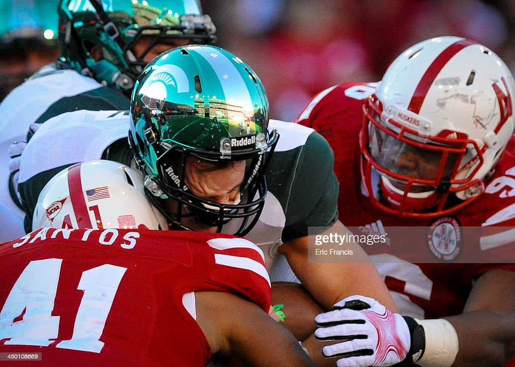 Quarterback Connor Cook #18 of the Michigan State Spartans gets crunched by defensive tackle Aaron Curry #96 of the Nebraska Cornhuskers and linebacker David Santos #41 of the Nebraska Cornhuskers during their game at Memorial Stadium on November 16, 2013 in Lincoln, Nebraska.