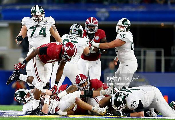 Quarterback Connor Cook of the Michigan State Spartans is sacked by defensive lineman Jonathan Allen of the Alabama Crimson Tide in the first half...