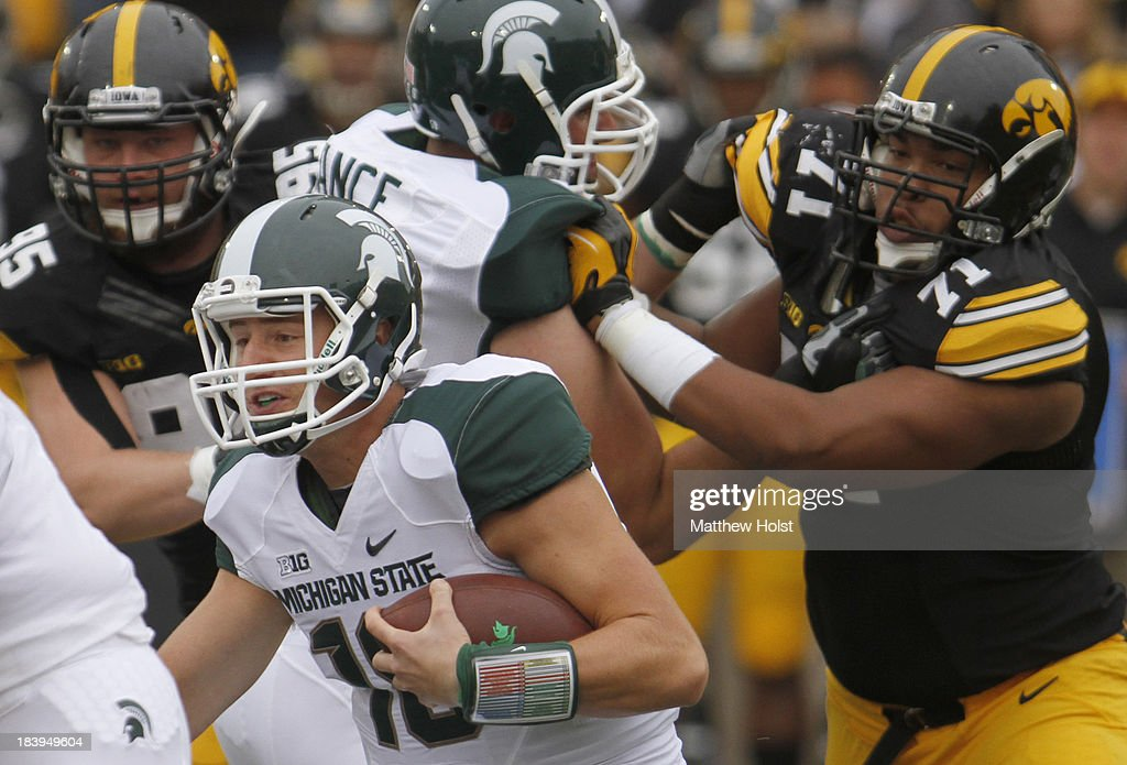 Quarterback Connor Cook #18 of the Michigan State Spartans runs on a keeper during the first quarter in front of defensive lineman Carl Davis #71of the Iowa Hawkeyes on October 5, 2013 at Kinnick Stadium in Iowa City, Iowa. Michigan State won 26-14.