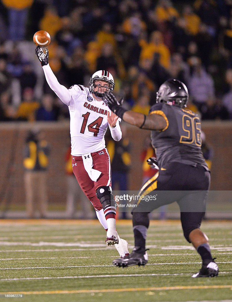 Quarterback Connor Shaw #14 of the South Carolina Gamecocks throws pass against pressure from defensive linemen Lucas Vincent 396 of the Missouri Tigers during the second half on October 26, 2013 at Faurot Field/Memorial Stadium in Columbia, Missouri. South Carolina defeated Missouri in double overtime 27-24.