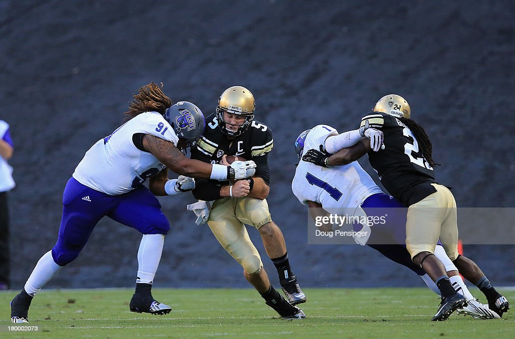Quarterback Connor Wood #5 of the Colorado Buffaloes scrambles for nine yards and a first down before being tackled by defensive lineman Matthew Hornbuckle #91 of the Central Arkansas Bears as wide receiver D.D. Goodson #21 of the Colorado Buffaloes puts a block on defensive back Karl Brady #1 of the Central Arkansas Bears at Folsom Field on September 7, 2013 in Boulder, Colorado.