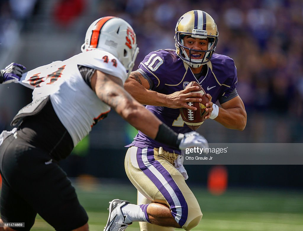 Quarterback Cyler Miles #10 of the Washington Huskies rushes against linebacker Jake Pele #44 of the Idaho State Bengals on September 21, 2013 at Husky Stadium in Seattle, Washington. The Huskies defeated the Bengals 56-0.