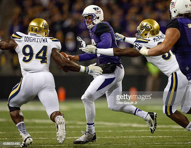 Quarterback Cyler Miles of the Washington Huskies rushes under pressure from Owamagbe Odighizuwa and Takkarist McKinley of the UCLA Bruins on...
