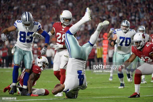 Quarterback Dak Prescott of the Dallas Cowboys dives into the endzone to score on a ten yard rushing touchdown against the Arizona Cardinals during...