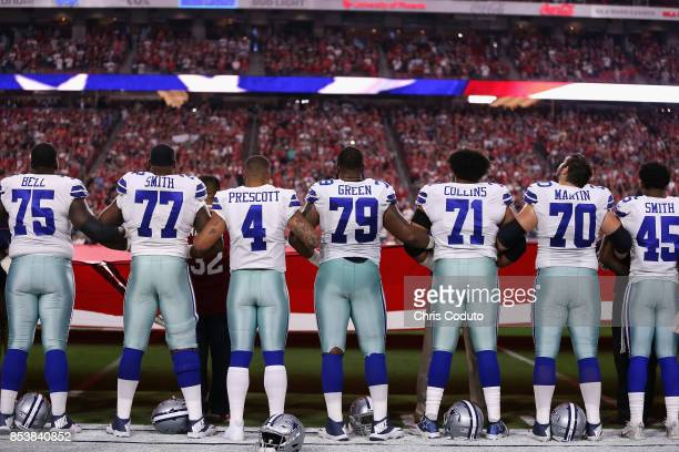 Quarterback Dak Prescott of the Dallas Cowboys links arms with teammates offensive tackle Tyron Smith and offensive guard Chaz Green during the...