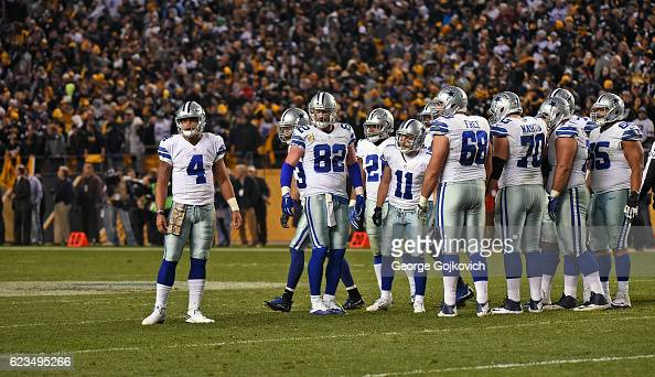 Quarterback Dak Prescott of the Dallas Cowboys looks to the sideline before huddling with members of the offense including tight end Jason Witten...