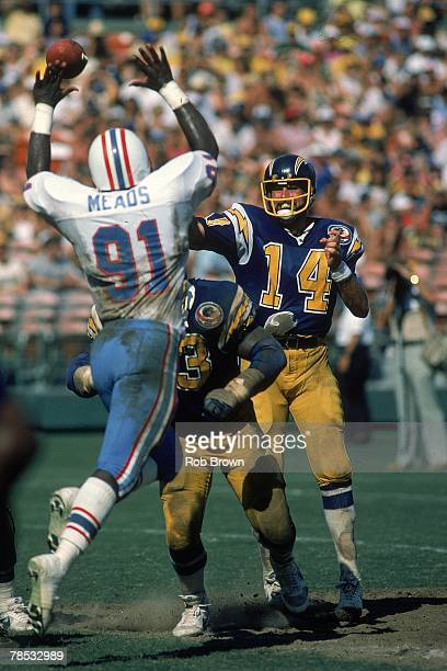 Quarterback Dan Fouts of the San Diego Chargers throws a pass over the outstretched hands of linebacker Johnny Meads of the Houston Oilers at Jack...