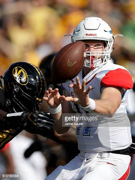 Quarterback Daniel Epperson of the Delaware State Hornets completes a shovel pass as defensive end Charles Harris of the Missouri Tigers defends...