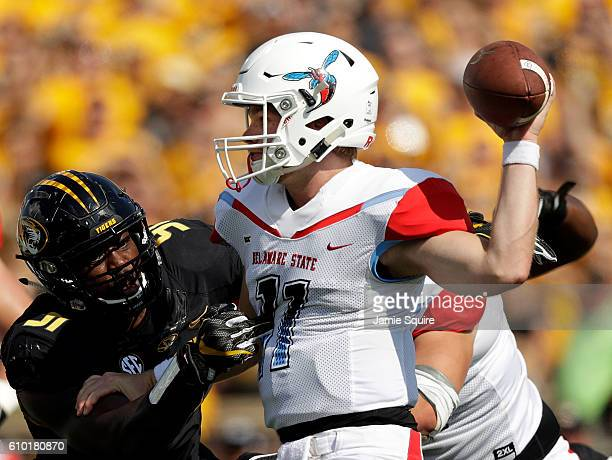 Quarterback Daniel Epperson of the Delaware State Hornets is sacked by defensive end Charles Harris of the Missouri Tigers during the game at Faurot...