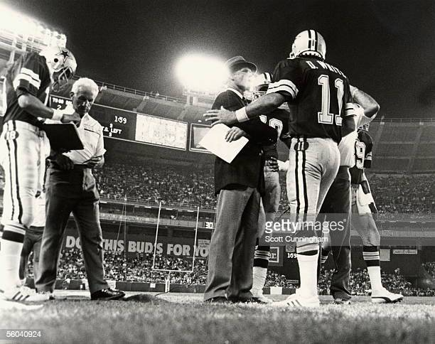 Quarterback Danny White of the Dallas Cowboys discusses a play with head coach Tom Landry during the game against the Washington Redskins at RFK...