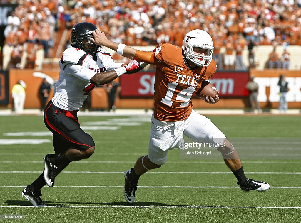 Quarterback David Ash of the Texas Longhorns stiff arms cornerback Derrick Mays of the Texas Tech Red Raiders in the second quarter on November 5...