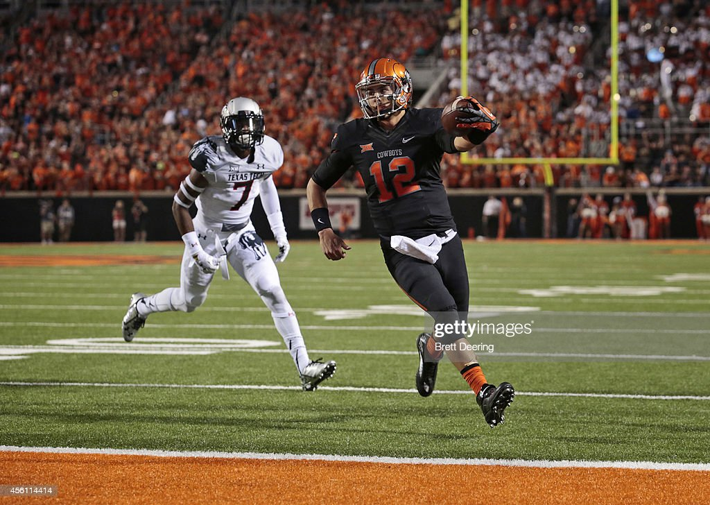 Quarterback Daxx Garman of the Oklahoma State Cowboys runs into the end zone in front of safety Josh Keys of the Texas Tech Red Raiders September 25...